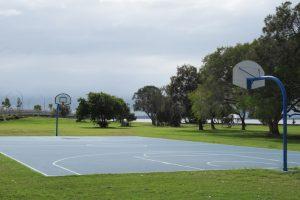 Basketball court, trees and grass at Decker Park.