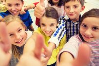 group of children giving thumbs up to the camera