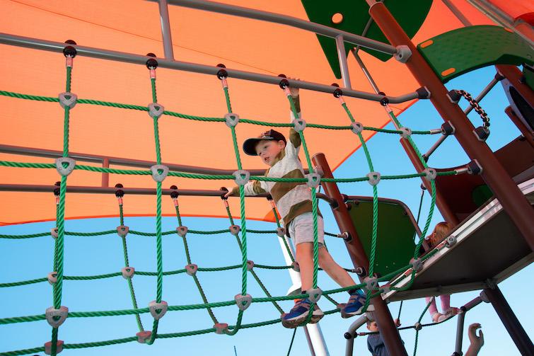 Boy crossing a rope bridge in playground.