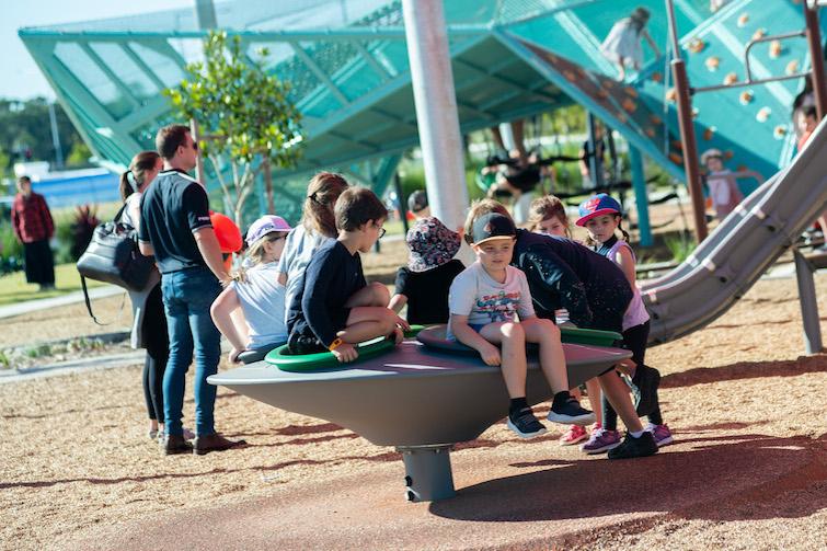 Children sitting in a multispinner carousel at Village Green playground.