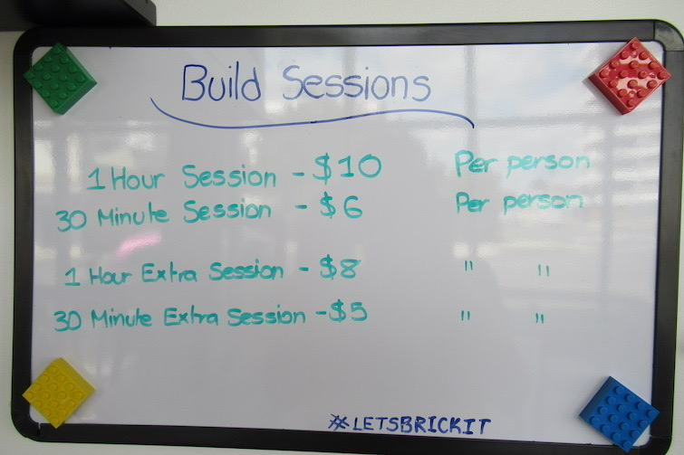 Whiteboard with session prices for Lego Building at Coffee n Bricks Cafe.